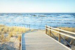 A wooden pathway to the Baltic sea at sunset. Sand dunes and plants in the background. Clear blue evening sky. Idyllic seascape. Latvia