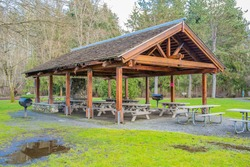 A WOODEN PICNIC SHELTER IN A LOCAL PARK WITH NUMEROUS PICNIC BENCHES