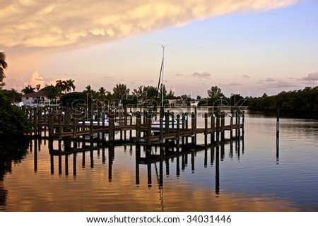 a wooden pier is reflected in the calm water as large clouds fill the sky at sunset.