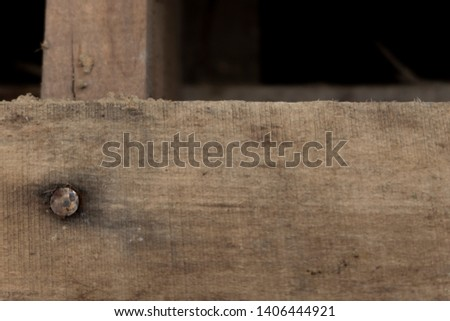A wooden plank with an old nail on it and even more planks bellow it