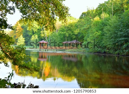 A wooden platform or pier with a roof as well as a wooden walkway situated next to a large river or lake reflecting autumn sky and trees in the middle of a dense forest or moor seen in Poland