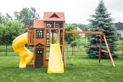 A wooden play structure and swing-set is centered on a grassy lawn. Includes two yellow slides,  two swings, a hanging gymnast bar and upper and lower fort areas. Trees fence and homes in background.