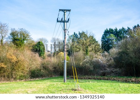 A wooden powerline pole with the powerline coming into the ground and lines to other poles .