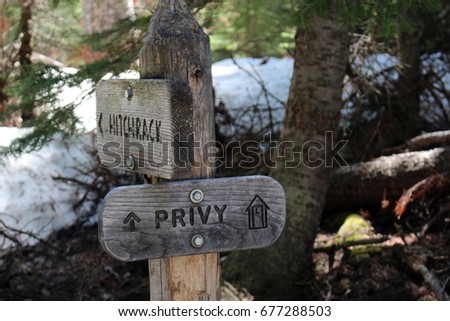 A wooden privy and hitchrack signpost on the Wild Basin Trail in Rocky Mountain National Park, Colorado, USA