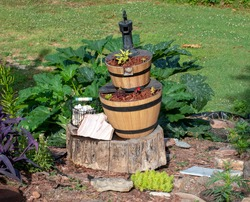 A wooden pump style fountain has been turned into the focal point of a backyard garden in southwest Missouri for a unique ornament of interest. Bokeh effect.
