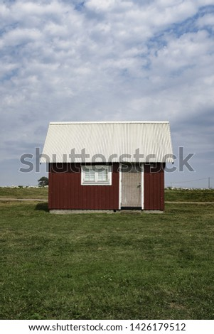 A wooden red barn with a white roof in a large green field with cloudy blue sky