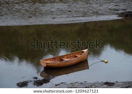 A wooden rowboat is left anchored in shallow waters