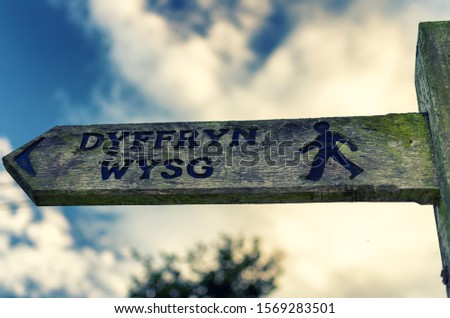 A wooden sign directing walkers in the direction of the Usk Valley, using the Welsh language Dyffryn Wysg