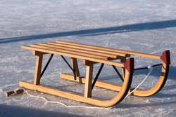 A wooden sledge with a pull rope is on the ice rink. There is no one on it