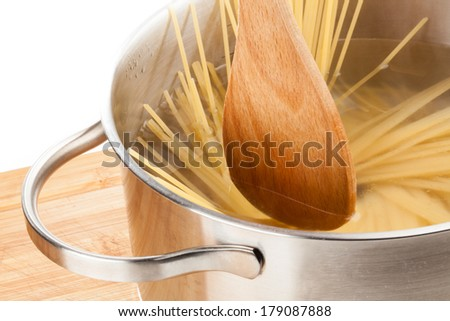 A wooden spoon is stirring some pasta in a pan which is filled with hot water.