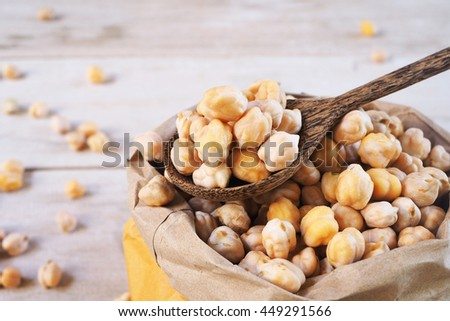 A wooden spoon of dried chickpeas on a chickpea bag.