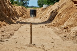 A wooden stakes for setting the height of the base of the pipeline for laying in the trench