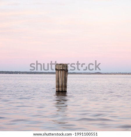 A wooden structure in the lake on background of an pink toned sunset