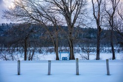 A wooden swing built for two and painted blue, faces the frozen Susquehanna River in Owego, NY during a cold, winter day after a snow storm.