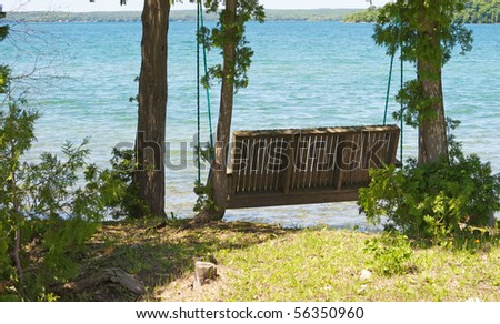 A wooden swing over the water rests in the shade by the for Swing over water