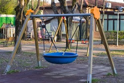 A wooden swing with a circular blue rubber seat in a public park (Pesaro, Italy, Europe)