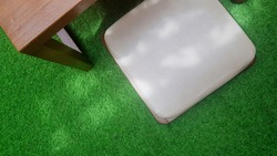 A wooden table and a Japanese seat cushion in a synthetic grass carpet with sunlight rays