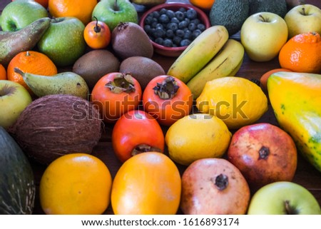 A wooden table full of lots of freshly picked fresh fruit. Many vitamins together on a wooden table.