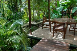 A wooden terrace with four chairs and a wooden slat table surrounded by a clear moat and thick foliage, palm trees and banana plants in the Caribbean.