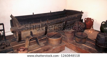 A wooden vat for grape-stomping, buckets and other antique household items in the basement of a traditional Bulgarian village house, Silistra Province, the South Dobrudzha region, Bulgaria