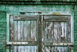 A wooden vintage scaled door at green bricks wall background.