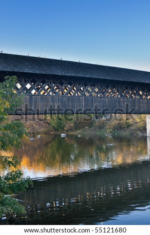 A wooden walking bridge, crossing the Speed river in Guelph, Ontario, Canada, on a calm autumn late afternoon.