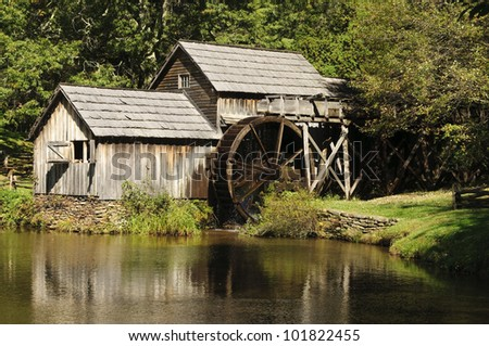 A wooden water mill with a lake