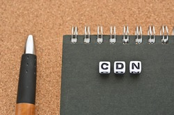 A word cube arranged in the shape of CDN sits on top of the notebook. It's an abbreviation for Content Delivery Network.