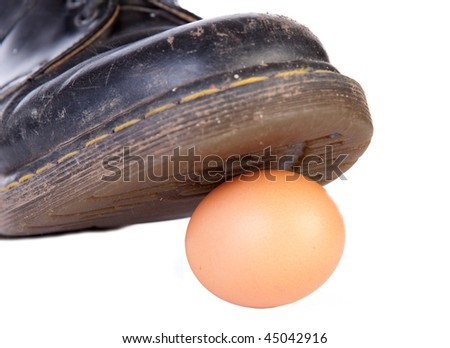 A work boot about to crush a raw egg symbolizing damage to something delicate or walking on eggshells