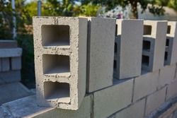 a worker builds a cinder block wall for a new home