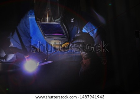 A worker by profession, a welder, closeups the details of a bearing in production. Photo without a face. The concept of professions with a risk to life. Photo in the interior.