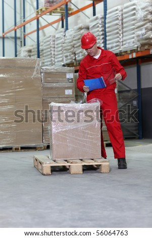 A worker checking inventory stocks at a factory storeroom.