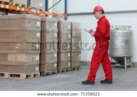 A worker checking stocks in a company warehouse.