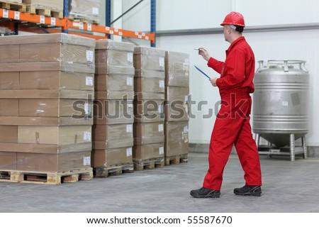 A worker counting stocks in a company warehouse.