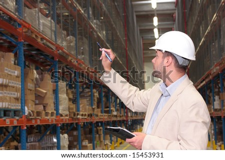 A worker counting the ready products stacked on the shelves in a factory storeroom.