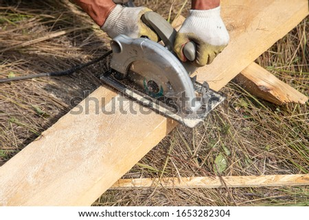 A worker cuts a wooden beam at a construction site.