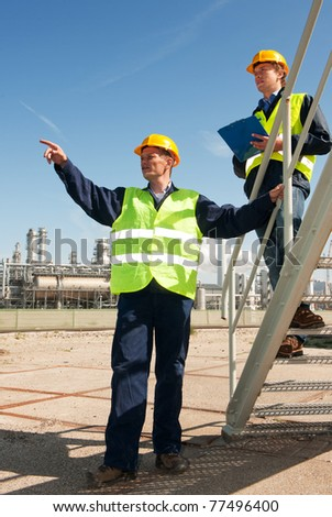 A worker discussing procedures with another worker in front of a petrochemical refinery