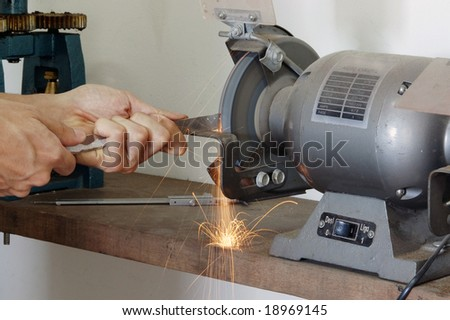 A worker grinding metal rod with sparks flying.