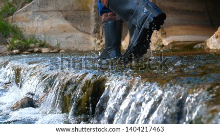A worker in a working uniform, rubber boots checks the sewage canal inside it and write down on paper all that. Polluted water flows from the water channel. Concept of: Recording, Testing, Quality. stock photo