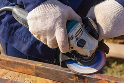 A worker in overalls is grinding a weld seam on a steel square profile pipe with an angle grinder with a flap disc.