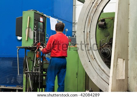 A worker in the metal industry with CNC milling machine.