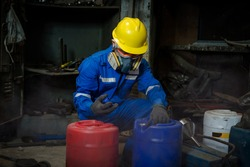 A Worker industry wearing safety uniform ,black gloves and gas mask under checking chemical tank in industry factory work