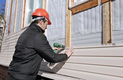 A worker installs panels beige siding on the facade of the house