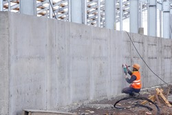 A worker is cleaning a concrete wall with a grinder. Preparing a flat surface on a concrete wall after installation