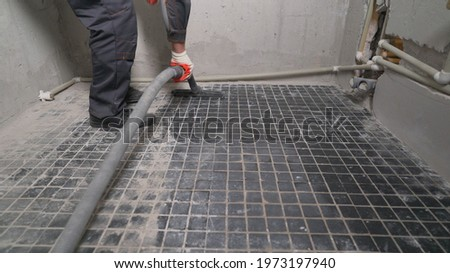 A worker is cleaning dust with a vacuum cleaner on the floor. Cleaning service. dust removal with vacuum cleaner. Worker removes dust with a vacuum cleaner. Worker vacuuming the floor before