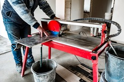 A worker is cutting a ceramic tile on a wet cutter saw machine.