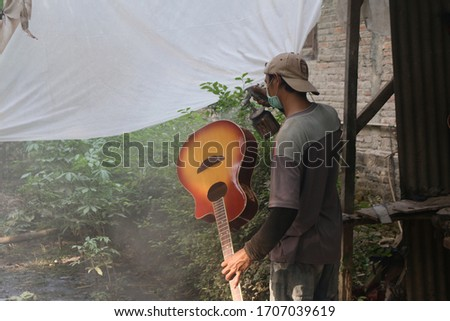 A worker is giving color to the guitar body in Baki, Sukoharjo, Central Java, Indonesia. Coloring is done carefully. 2016 photo