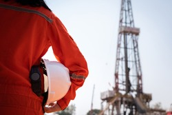 A worker is holding safety hardhat or helmet with blurred background of drilling rig derrick structure, selective focus at hardhat. Ready to working in oil field industrial concept photo.