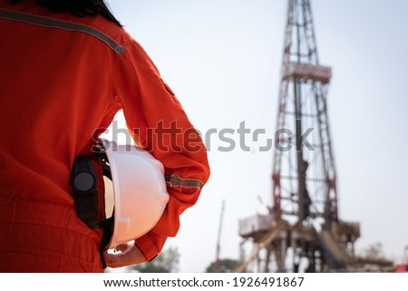 A worker is holding safety hardhat or helmet with blurred background of drilling rig derrick structure, selective focus at hardhat. Ready to working in oil field industrial concept photo. Stockfoto ©