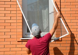 A worker is installing a window mosquito net, fly screen or insects screen to protect the house from insects in summer.